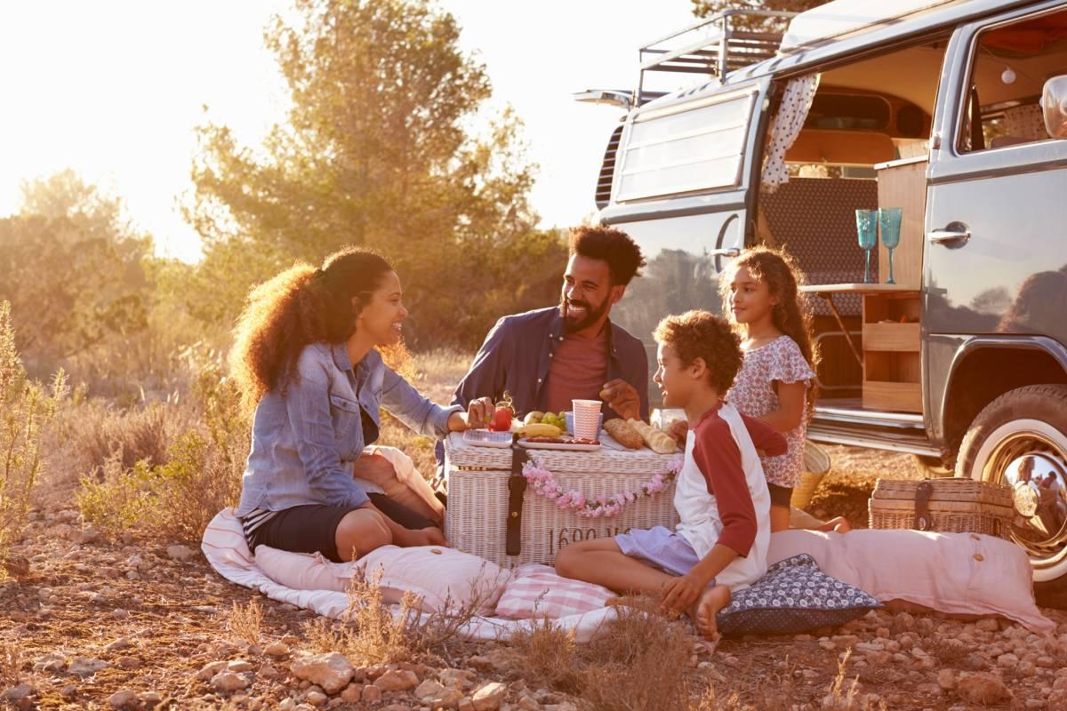 famiglia con figli piccoli e adolescenti si gode la vacanza in camper